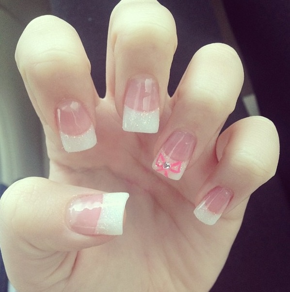 White sparkly tips, pink bow with gem acrylic nails ...