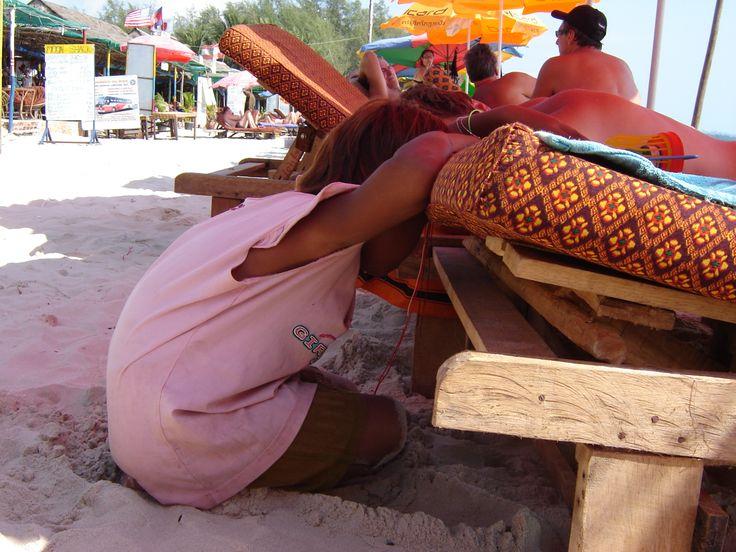 Een veel te jong strandverkoopstertje dat in slaap valt tegen het strandbed. Hartverscheurend, Cambodja
