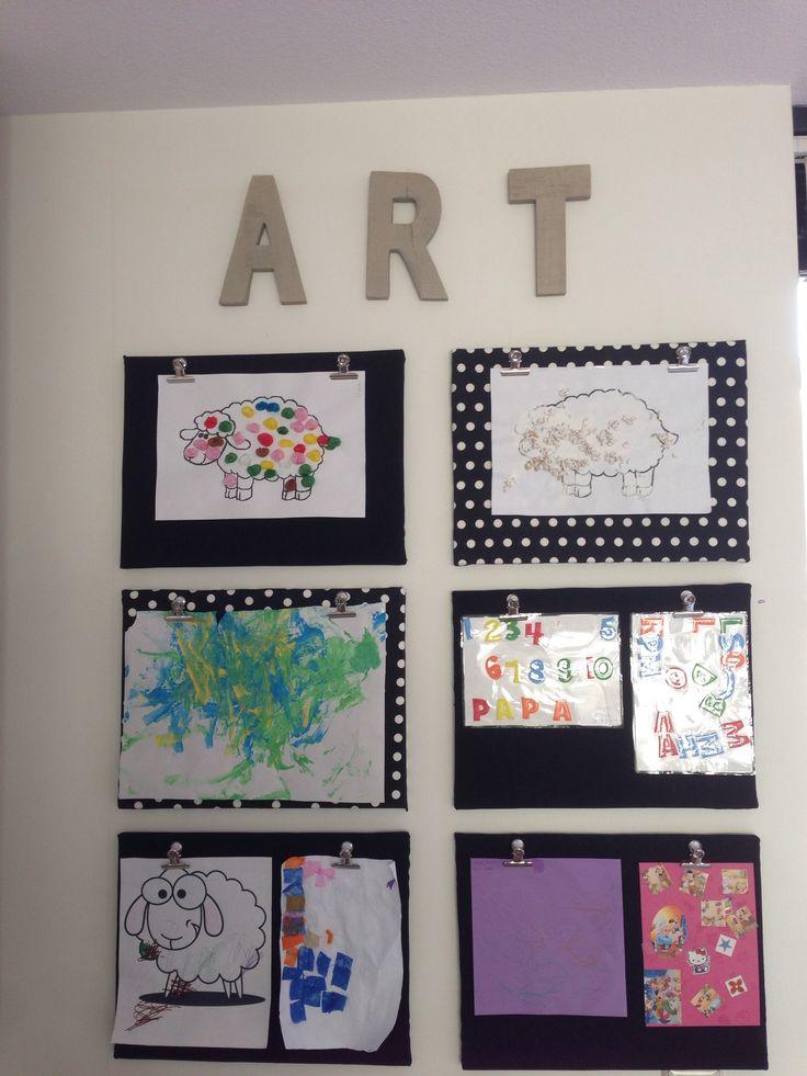 Kunstwerken van de kinderen ophangen in de speelhoek.