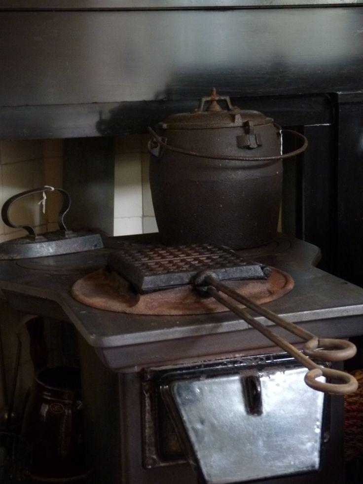 Antieke gietijzeren snelkookpan, wafelkijzer en strijkijzer op een antiek kacheltje.