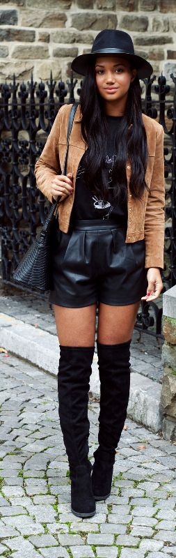 black hat + black graphic tee + camel suede jacket + black purse + black leather shorts + black suede thigh high boots