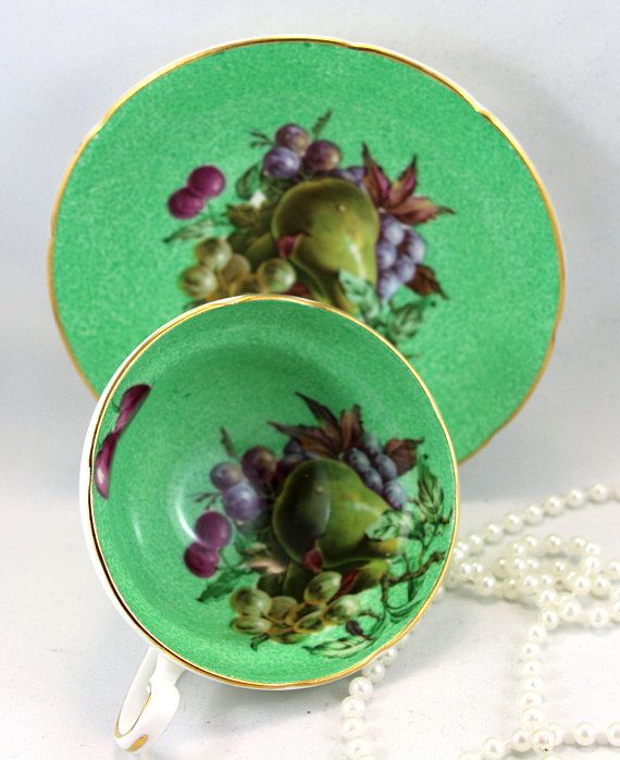 Old Royal Teacup & Saucer, Fruit Pattern on Green Background, Gold Rims, Bone English China made in 1960s. In good condition, no chips, cracks, crazing or repairs. The Saucer measures-5.5 (14cm) in diameter. The Cup opening-3.7 (9.5cm), with the Handle-4.5 (11.5cm) The Height-2 (5cm)