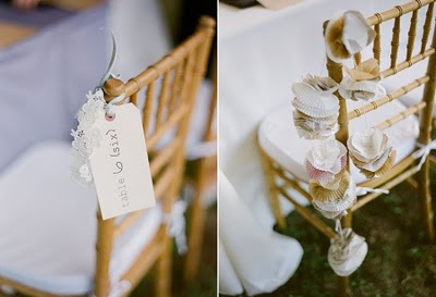 Lacey details, strings of pearls and vintage style ribbons held table cards to chairs , and home made garlands made from cupcake liners in whimsical colors and patterns adorned chair backs and tent poles