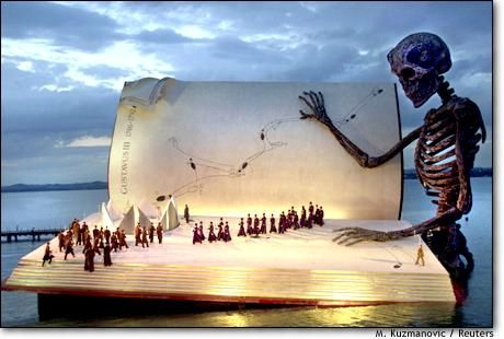 """""""Singers perform on a giant stage on Lake Constance during a rehearsal of Giuseppe Verdi's opera 'Ein Maskenball' on July 15. The design of the stage in the lake shows 'Death' reading the book of life."""""""