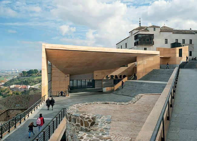 El Greco Congress Center, Rafael Moneo, Toledo, Spain.  Moneo designed the signage for the porchlike entry, which opens to the street leading up to the city center. Stairs and exterior paving are made of basalt, and walls are of poured concrete.