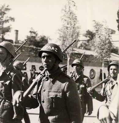 Αγωνιστές του ΕΛΑΣ βαδίζουν συντεταγμένα στην Διονυσίου Αεροπαγίτου, λίγο μετά την απελευθέρωση. Πίσω, ο τοίχος του παλιού Στρατιωτικού Νοσοκομείου στην περιοχή Μακρυγιάννη, με κάποια διαφήμιση (Οκτώβριος 1944)