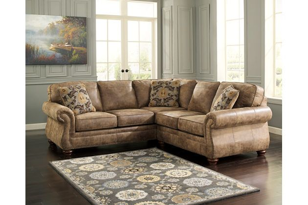 Dramatically transform your living space with the rustic look of weathered leather you love, at a fraction of the cost. That's the beauty of the Larkinhurst faux leather 2-piece sectional. Washed in earthy Southwestern tones, with generous back and seating support and jumbo window-pane stitching—it envelopes you in comfort and quality. Classic elements such as rolled arms and turned feet bring in just enough traditional touch.