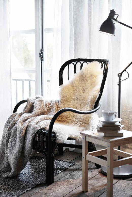 Eine Kuschelecke. Der ideale Ort für entspannte Leseabenteuer. STORSELE Sessel mit hoher Rückenlehne in Schwarz/Rattan mit verschiedenen Textilien, LUDDE Schaffell