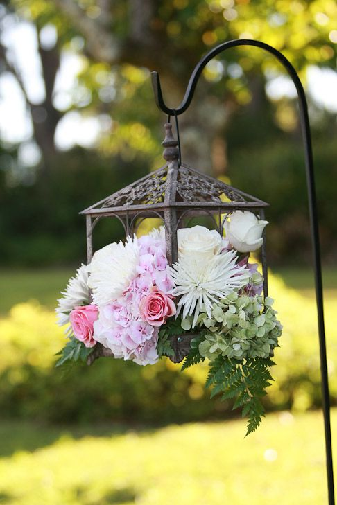 Hanging wedding flowers in a lamp on a shepherds hook. Would be pretty in the backyard for shower, rehearsal dinner, or day after luncheon