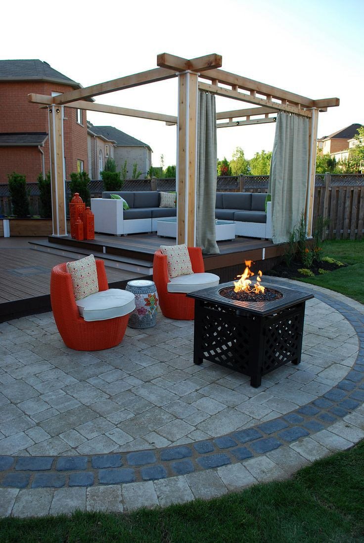 """A semicircular stone patio is home to a cozy gas fire feature on """"Decked Out"""" project """"The Lounge Deck"""".  Deck Design by Paul Lafrance Design."""