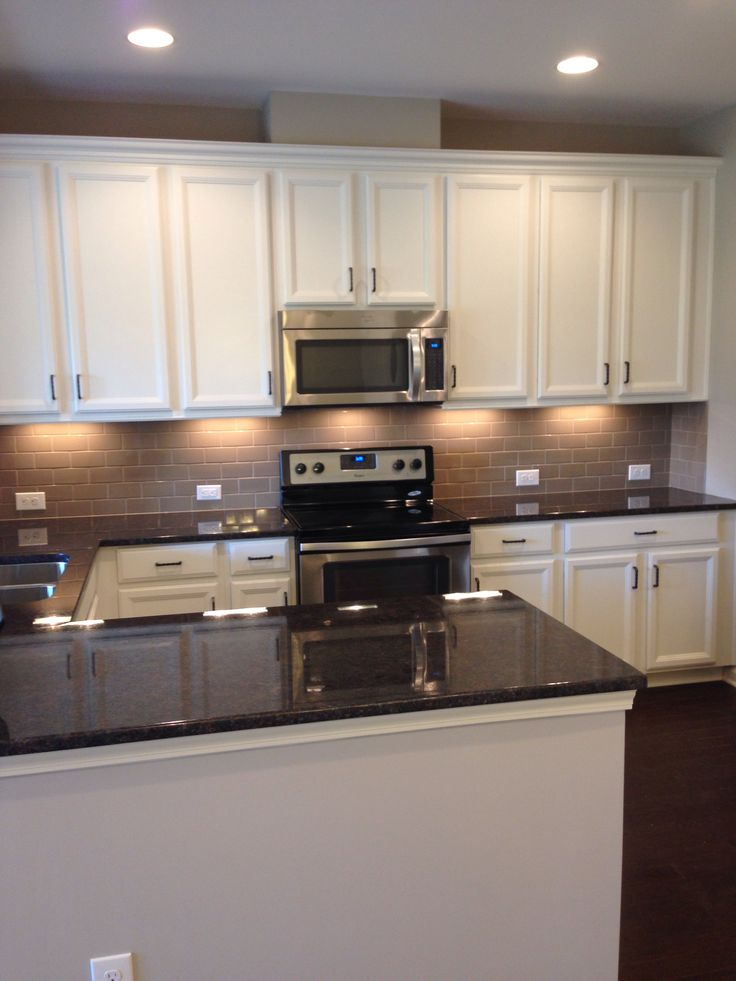 My new kitchen white cabinets tan subway tile backsplash for Brown kitchen cabinets with black appliances