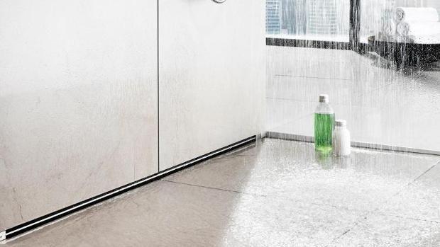 Neue Ideen für die Dusche: Statt über einen klassischen runden Ablauf mitten in der Bodenfläche fließt das Wasser nun in Rinnen ab. Foto: Vereinigung Deutsche Sanitärwirtschaft/Viega - DPA