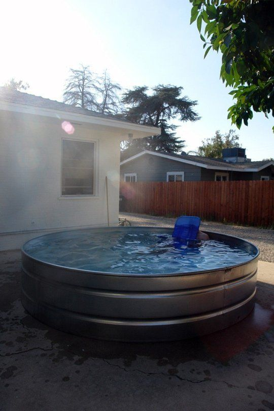 Backyard with a large round stock tank turned into a swimming pool