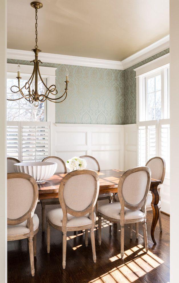 Пример элегантной столовой в английском стиле с неброскими глянцевыми обоями, оттененными белым деревянным молдингом. Цвет и фактура натурального дерева: обеденный стол и стулья, пол. Изюминка интерьера – люстра из латуни