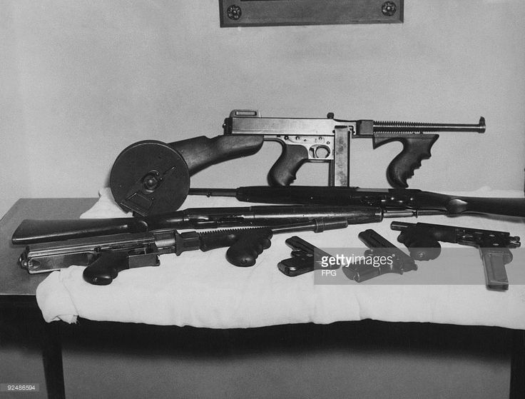 A collection of weapons used at various times by American bank robber John Dillinger, 25th July 1934. The guns, which were taken by federal agents in raids at St Paul and Spider Lake, Wisconsin, are on display at the Department of Justice in Washington DC. The small Colt .38 automatic was in Dillinger's possession when he was shot in Chicago on 22nd July. Also pictured are two machine guns, two rifles and a .45 automatic which has been converted into a machine gun.