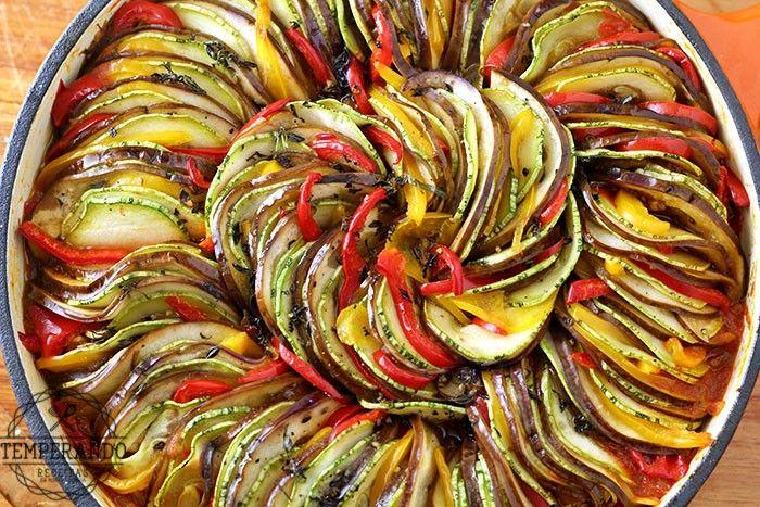 Receita de um delicioso ratatouille. Vegetais intercalados com um delicioso molho de tomate em uma apresentação linda que vai ser a atração da sua refeição.