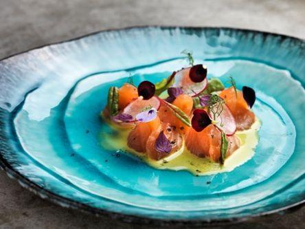 Salmon sashimi with yuzu dressing, orange juice and parsley chips