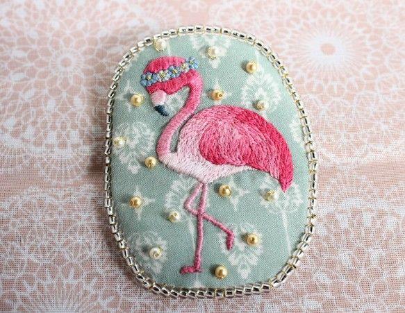 青い花冠をかぶってご機嫌なフラミンゴの刺繍ブローチです。お洋服やバックなど‥さりげなく、華やかさをプラスしてくれます。インテリアとして、お部屋の好きなところに飾っても♪◎size:5.8×7.5◎素材:刺繍糸・綿生地・透明&ナチュラルカラービーズ・厚紙・ブローチピン:注意事項:○ブローチピンは金属製の物を使用しています。 アレルギー等ございましたら付け替え可能ですので、 遠慮なくお申し付け下さい。○実物に近い色味になるよう撮影を心がけておりますが、 お使いのPCや端末の画面によって、写真と実物の色味が 若干異なって見える場合がございます。○とても繊細な商品となっていますので、衝撃・水濡れ等にご注意下さい。○既製品と比べると、縫い方などに劣る点があるかと思います。 ハンドメイドの味として、楽しんで頂けたら幸いです。以上、ご了承下さい。何かご不明な点・気になる点がございましたら、遠慮なくお申し付けください:)