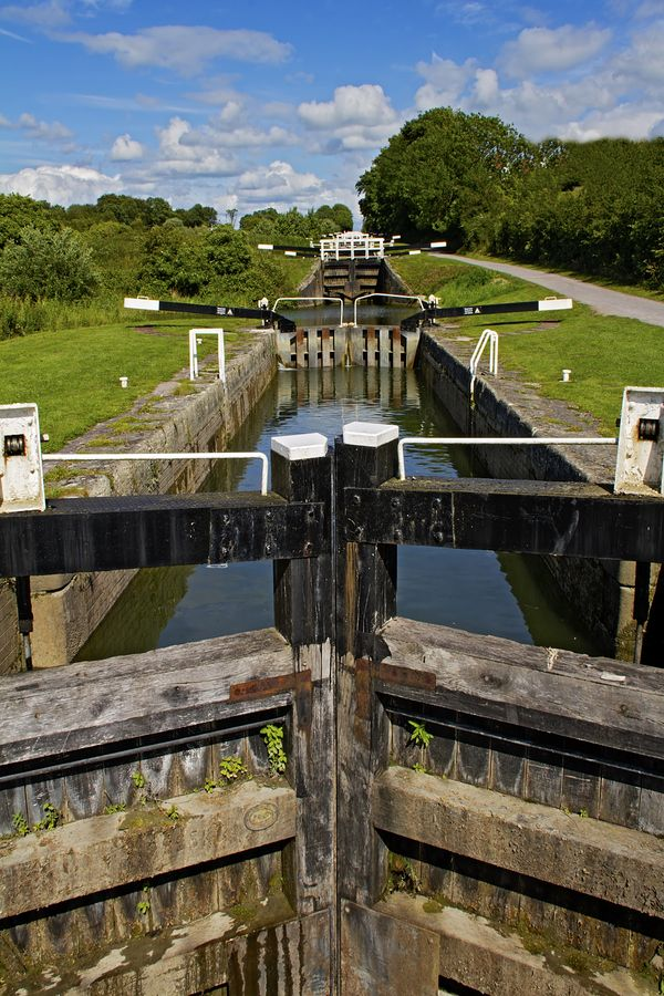 Caen Hill Locks are a flight of locks on the Kennet and Avon Canal, between Rowde and Devizes in Wiltshire. A lock is a device for raising and lowering boats between stretches of water of different levels on river & canal waterways. Locks are used to make a river more easily navigable, or to allow a canal to take a reasonably direct line across land that is not level.