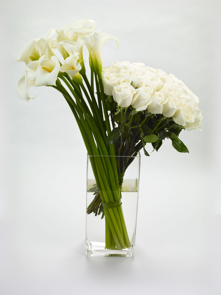 Two Tall Arrangements Of White Calla Lilies And Roses Side By In The Same
