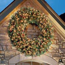 A gorgeous over-sized outdoor Christmas Wreath::I love the simple use of greens with gold embellishments.