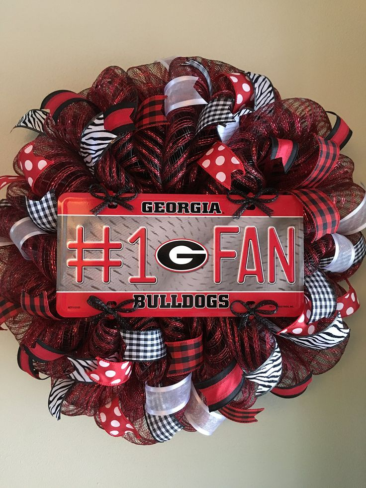 "Georgia Bulldogs Mesh Wreath. This wreath is made on a high quality black and red striped mesh. It features a Georgia Bulldogs #1 Fan centerpiece surrounded by lots and lots of black, red and white wired ribbons. What a great way to show your support for your favorite team. This wreath measures approximately 23"" in diameter."