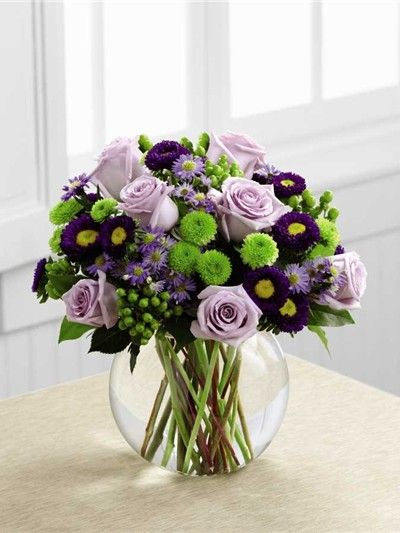 Bubble bowl vase with green flowers and lavender flowers including lavender roses