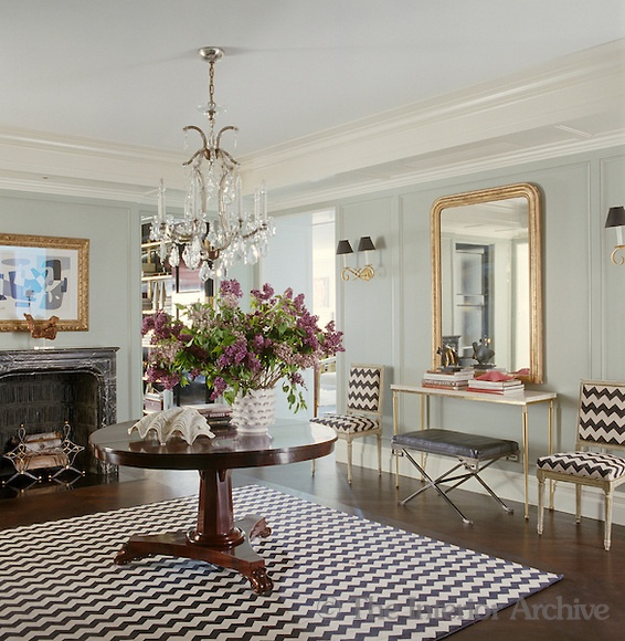 In the entrance hall an antique pedestal table takes centre stage on a rug with a striking herringbone pattern, which is also used to cover a pair of matching hall chairs on either side of a gilt mirror and console table