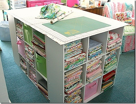 Sewing room. Bookcases in a square and cutting board on top.
