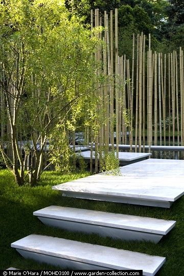 Steps up to a contemporary Japanese garden using a floating stone path above the water and vertical bamboo sticks as an architectural feature.