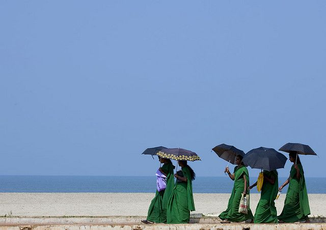 Group Of Young Women In Green Saris Holding Umbrellas Walking Down Alleppey Beach, India by Eric Lafforgue #India #Photography