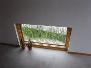 土間にある地窓です。ここは庭をながめるためだけの窓です。その向こうに見える庭には、砂利を敷き詰め、トクサという和風な感じの植物を植えてあります。春には、ツクシのようにニョキニョキと砂利のあいだから伸びてきました。
