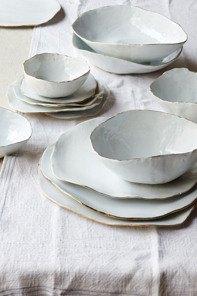 These uneven bowls and plates are the work of Laura Letinsky, made from ceramic with shiny gold rims.