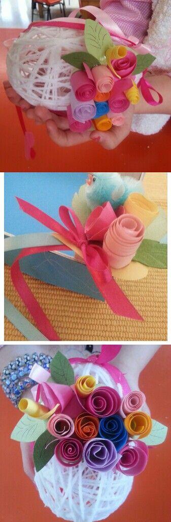 Uovo realizzato con filo bagnato in colla vinilica e arrotolato attorno a un palloncino.Decorato poi con fiori realizzati con strisce di carta arrotolata