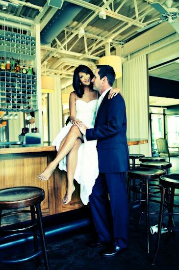 The bride & groom pose by the bar, at Print Works Bistro, in the Proximity Hotel, Greensboro