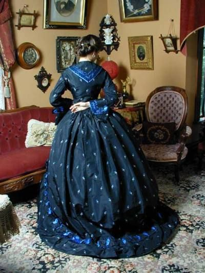 1860's Day dress of black silk with embroidered flowers in blue and silver; the trim is blue silk under black lace.