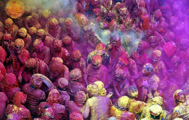 Hindu devotees throw colored powder at the Radha Rani temple during the Lathmar Holi festival in Barsana on March 21, 2013.