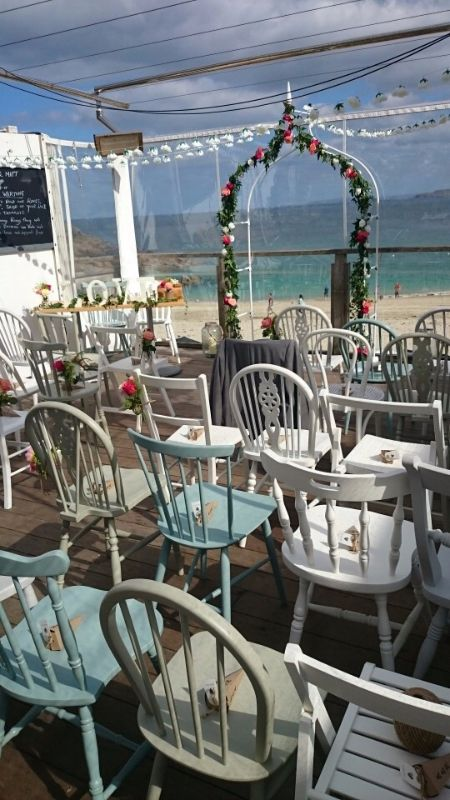 Stunning beach view wedding ceremony at Porthgwidden Beach Cafe, St Ives.  Using a mismatched combination of white, french grey and persian blue chairs