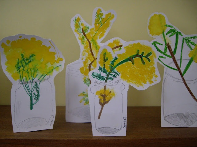 felt pen vases, stems and leaves, yellow paint to create the fluffy texture of wattle, with heavy cardboard stand at the back.