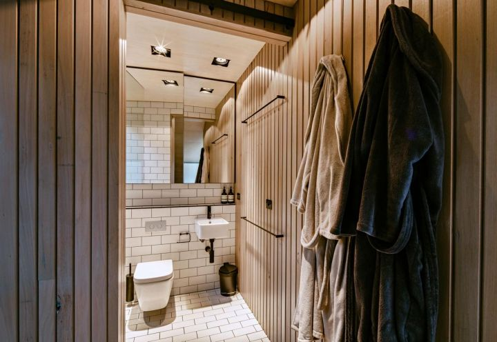 Compatto nelle dimensioni, ma confortevole, il bagno dell'abitazione firmata Maddison Architects a qualche chilometro da Victoria, in Australia, alterna rivestimenti in ceramica bianca e doghe di legno naturale con un effetto caldo