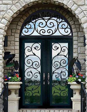 Beautiful Wrought Iron double doors and potted urns with flowers and arch