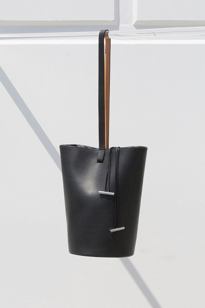 Building Block Smooth Leather Basket Bag - Silver drawstring hardware - One piece smooth black Italian leather - Resin lined interior - Black and nude leather shoulder strap - Lamb leather cinch closu