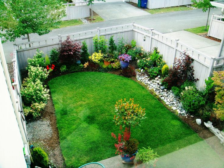 "Small backyard garden. This person didn't care for the grass and replaced it with concrete and stone. I personally love to see grass in the yard. It looks so inviting and lush and sets off the flowerbeds nicely. This ""before picture of the backyard"" is pretty."