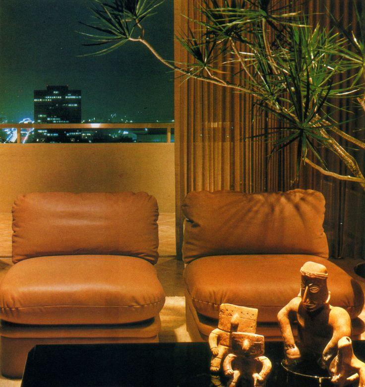 80sdeco: stuffed leather chairs, ancient artifacts on a black lacquer table, mature palm, and city viewsupremeinteriorsContemporary Apartments | Architectural Digest ©1982