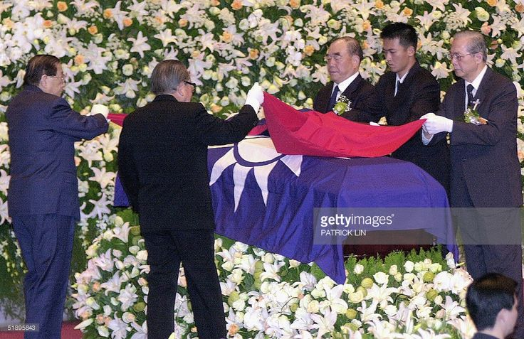 Four senior members of the opposition Kuomintang (KMT) party drape a Taiwan national flag on the coffin of the former first lady Chiang Fang-liang, wife of former president Chiang Ching-kuo, at a funeral service in Taipei, 27 December 2004.