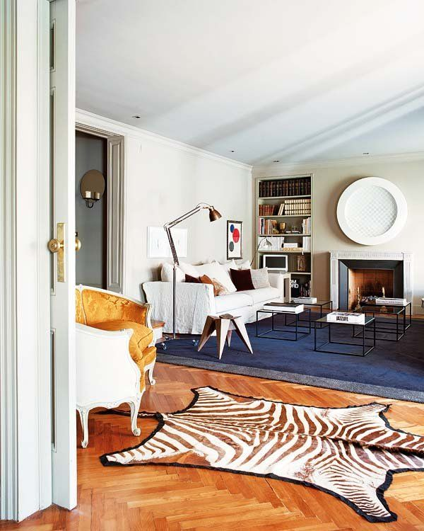 A graphic zebra rug draws attention to stunning chevron parquet floors.