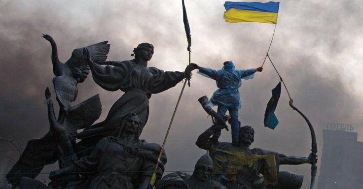 Imagem 1/10: 20.fev.2014 - Um manifestante anti-governo esgue a bandeira da Ucrânia no topo de uma estátua durante confrontos com a polícia ...
