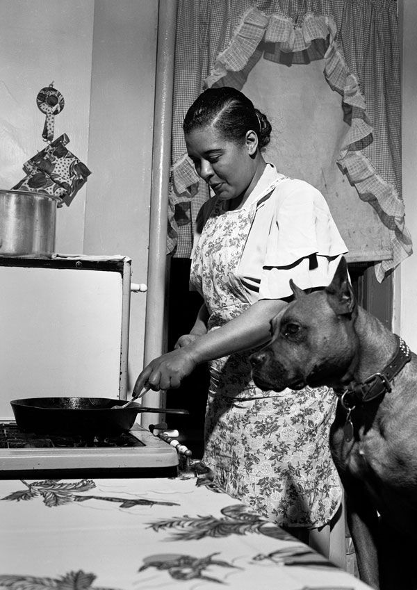 Billie Holiday cooks a steak for her dog Mister in her apartment in the Harlem neighborhood of New York. Photo: Herman Leonard  (1949)