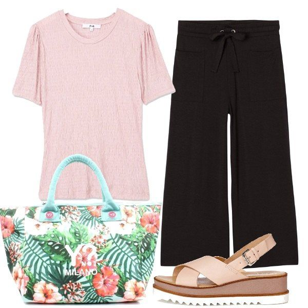 Un semplice outfit composto da pantaloni ampi con coulisse e tasche, la maglia lavorata rosa e i sandali platform hanno un mood moderno e colorato grazie alla bella borsa con disegni tropicali.