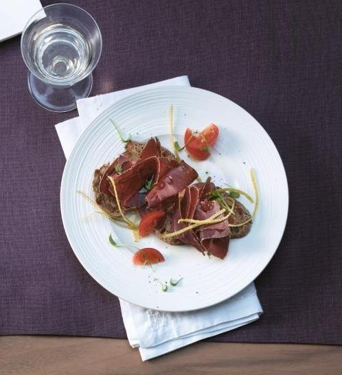 Walliser Trockenfleisch Mariniert mit Zitronenschale, Kirschtomaten und Zitronenthymian, serviert auf geröstetem Feigenbrot